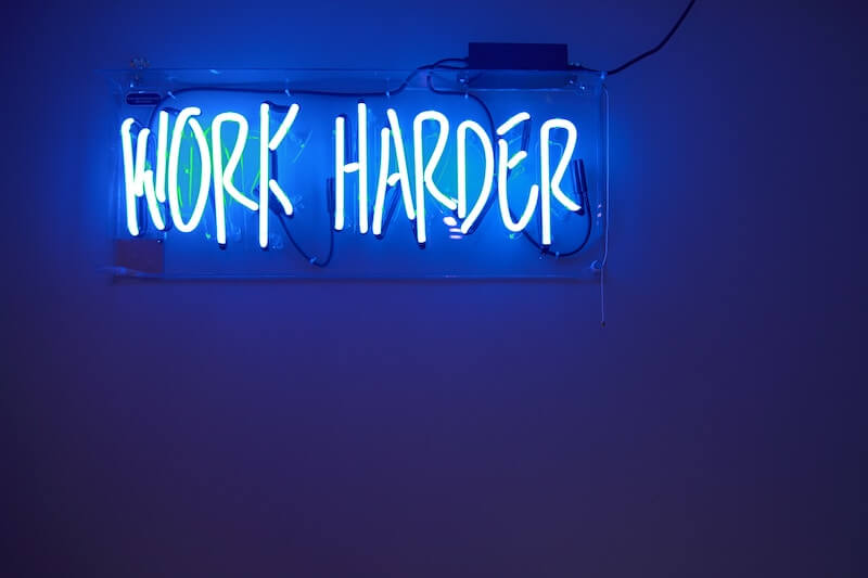 "A blue neon sign spelling out the words ""Work Harder"""