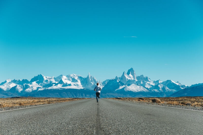 A man running along a road towards some mountains.