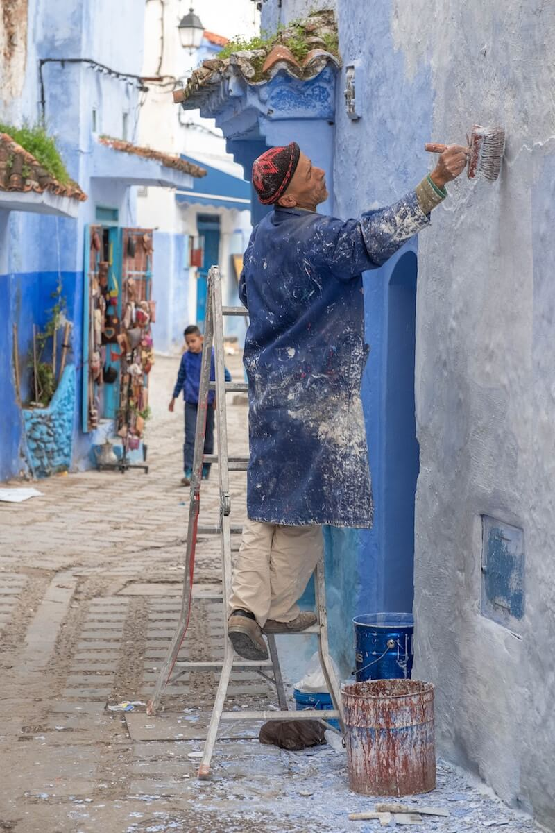 A man painting a house blue in Chefchaouen