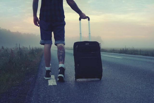 A man walking down a road dragging a suitcase behind.