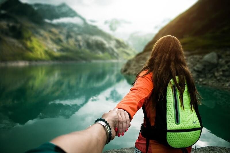 Two people holding hands by a lake