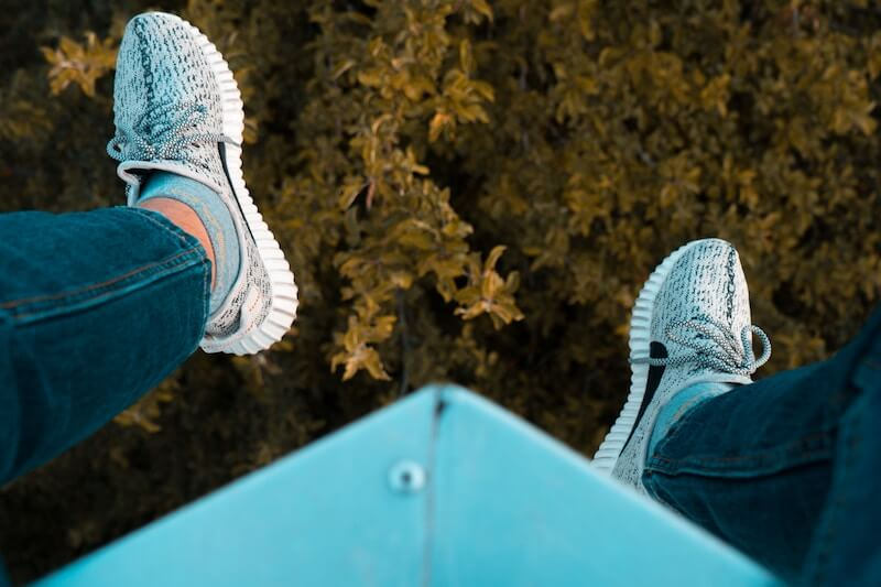 Legs hanging over a forrest below