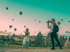A man taking a photo of a woman standing in front of many hot air balloons in the sky.