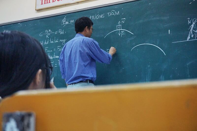 A teacher drawing on a chalkboard