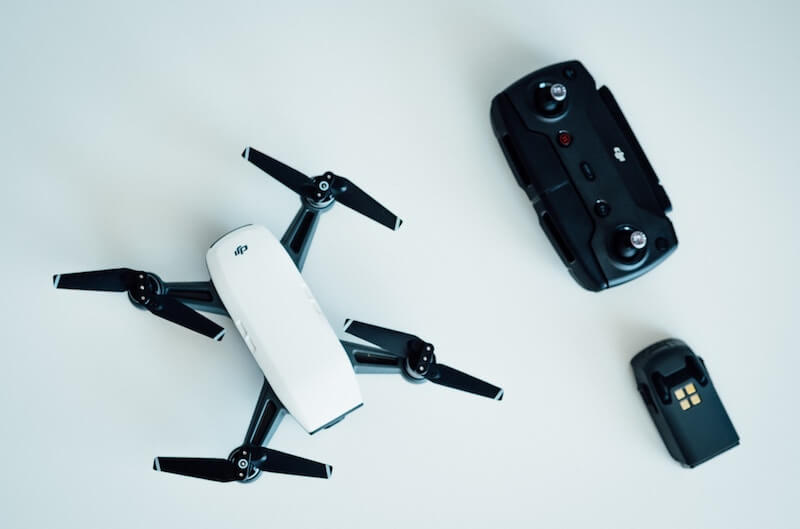 A DJI Spark drone on a white table with a controller and battery next to it
