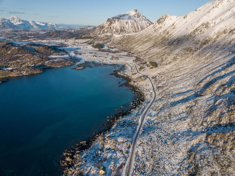 A snow-covered road running between a lake and a mountain in Norway