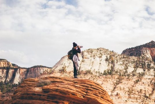 A man standing on a rock taking a photo