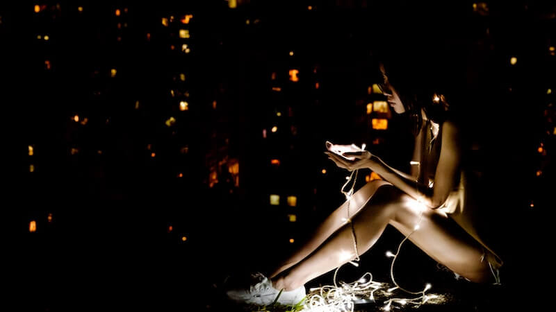 Girl sitting in the dark lit up by fair lights