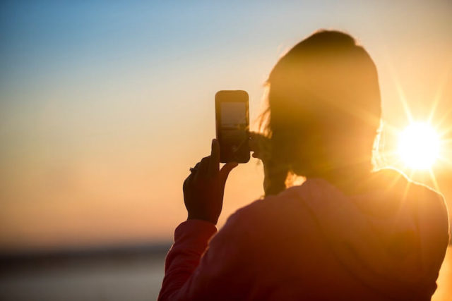 A person holding up a mobile phone taking a picture of a sunset