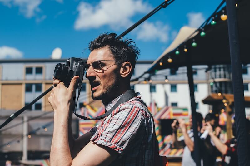 A man holding a camera up to his face