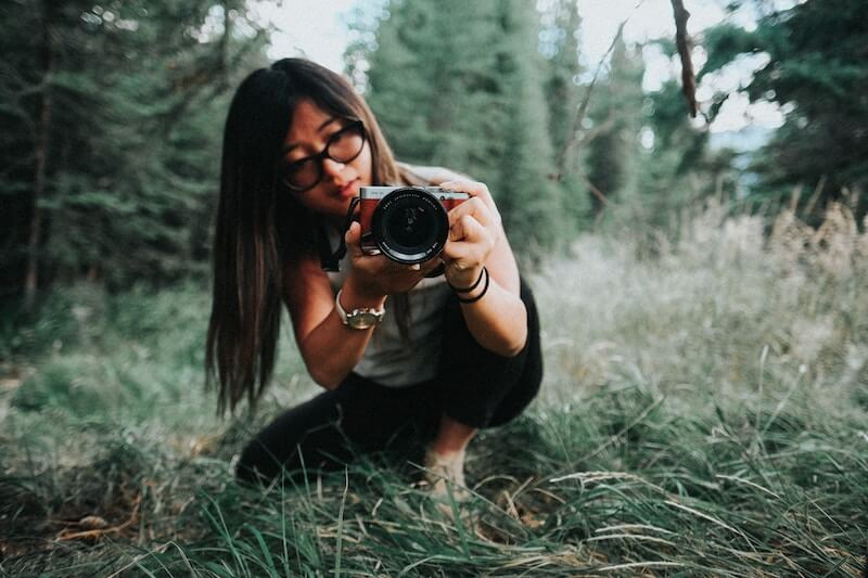 A girl crouching down in the grass taking a photo