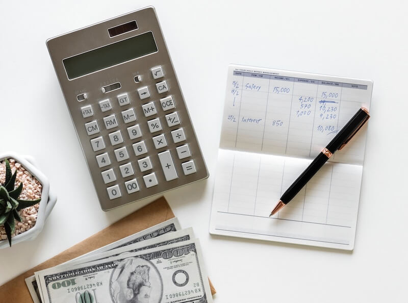 A calculator, dollar bills and notepad on a white table