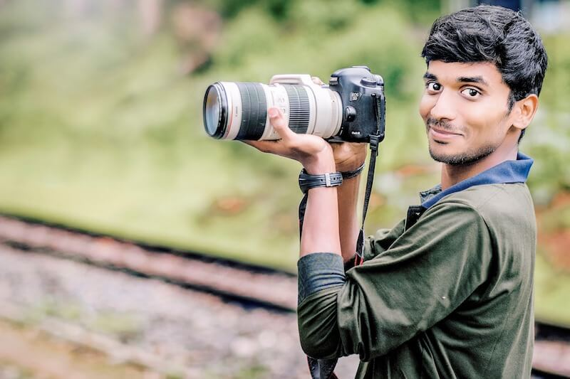 An Indian man holding a camera with a telephoto lens